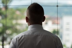 Young Businessman Looking Out Office Window Pondering Future